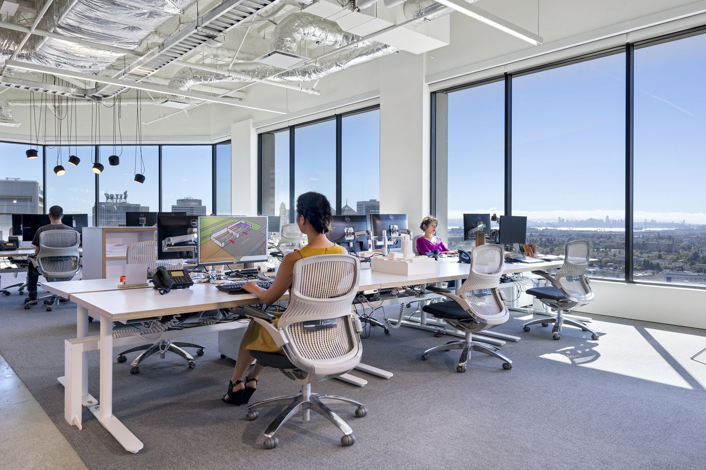 Employees utilizing their open floor plan to operate their business